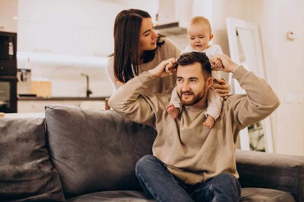 Junge familie mit babykleinkindmädchen zu hause, das auf sofa sitzt
