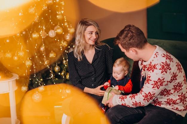 Junge familie mit dem baby, das durch weihnachtsbaum sitzt