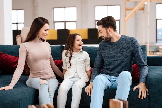 Junge familie mit dem kleinen mädchen, das auf sofa sitzt.