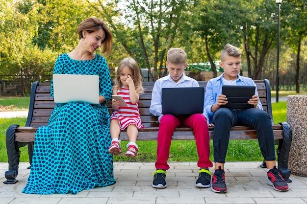 Junge familie mit den geräten, die auf der bank sitzen