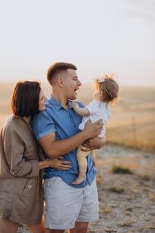 Junge familie mit der kleinen tochter auf dem sonnenuntergang in einem feld