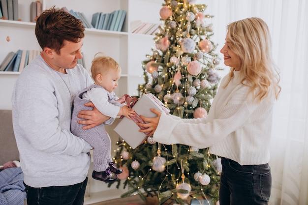 Junge familie mit der kleinen tochter, die weihnachtsgeschenke hält