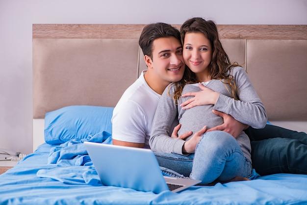Junge familie mit der schwangeren frau, die baby im bett erwartet