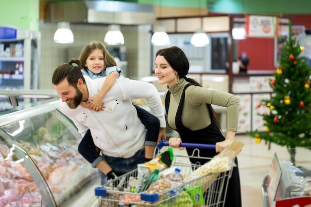 Junge familie mit einem kleinen mädchen, das in einem großen supermarkt einkauft. konzept eines neuen jahres.