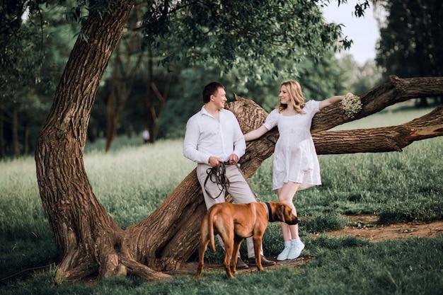 Junge familie mit ihrem hund, der in der nähe eines großen baumes steht