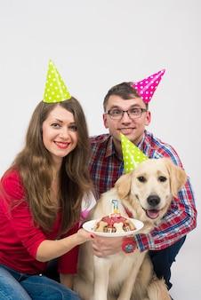 Junge familie mit ihrem hund golden retriever feiern ein jahr geburtstag.