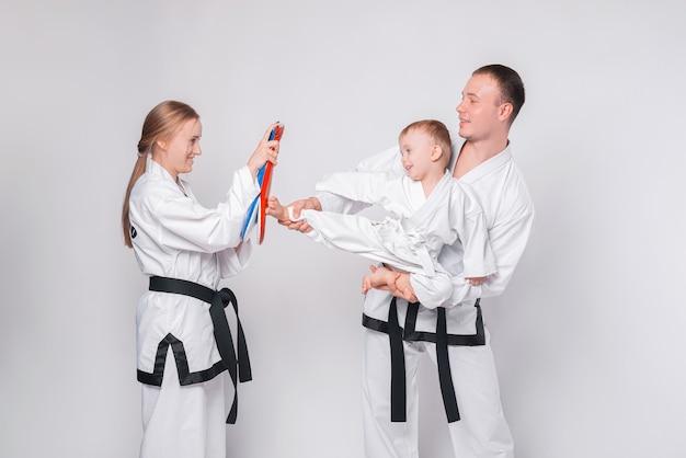 Junge familie mit ihrem kleinen jungen, der kampfkunst auf weiß praktiziert