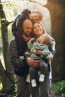 Junge familie mit ihren kindern, die spaß im wald haben
