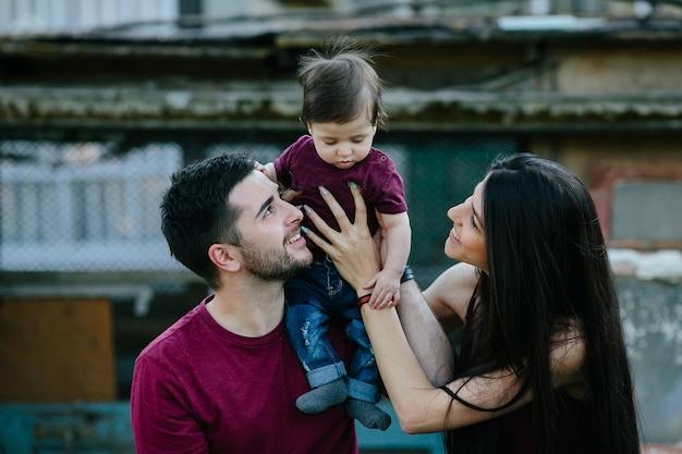 Junge familie mit kind, das auf einem verlassenen gebäude aufwirft