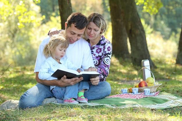 Junge familie mit kind, das die bibel in der natur mit picknick liest