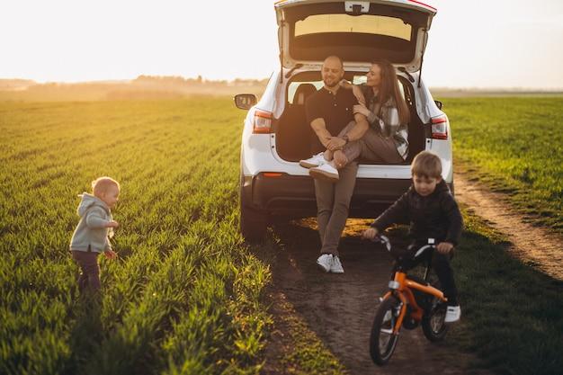 Junge familie mit kindern, die mit dem auto reisen, hielt auf dem feld an