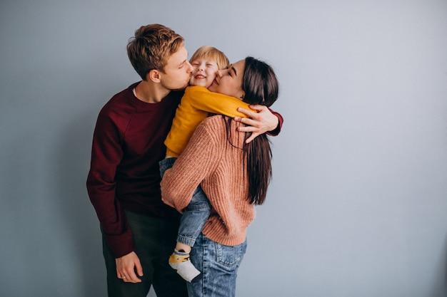 Junge familie mit kleinem sohn zusammen auf grau