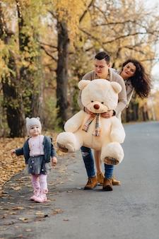 Junge familie mit kleiner tochter am anwesenden großen bärnspielzeug der herbstparkstraße