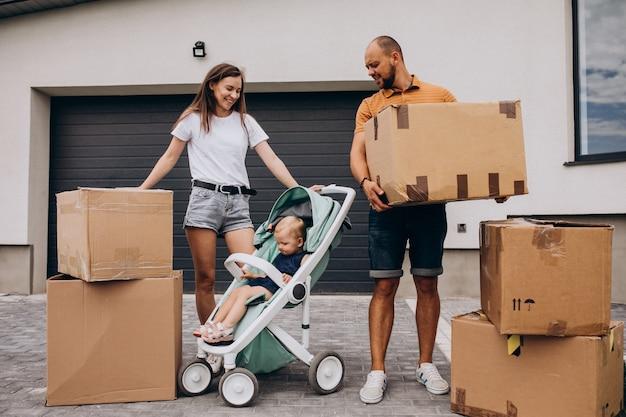 Junge familie mit kleiner tochter, die in neues haus einzieht