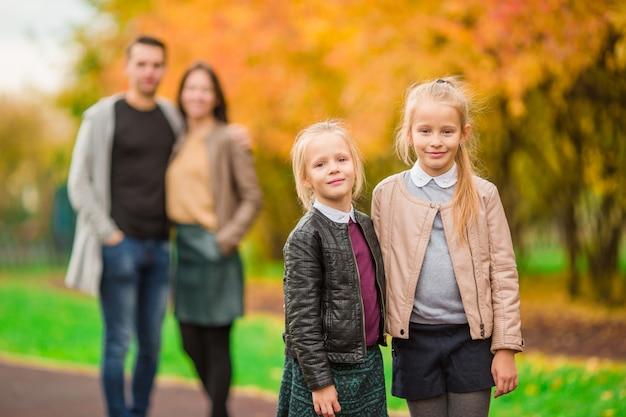 Junge familie mit kleinkindern im herbstpark am sonnigen tag