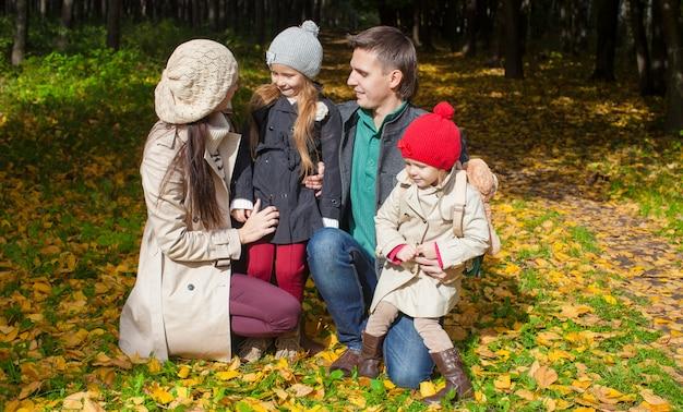 Junge familie mit netten kleinen mädchen im herbstpark am sonnigen tag
