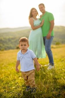 Junge familie mit niedlichem kleinen jungen, der spaß draußen im sommerfeld hat