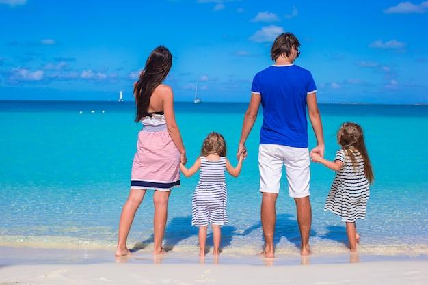 Junge familie mit zwei kindern am tropischen weißen strand