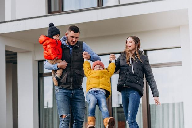 Junge familie mit zwei kleinen brüdern am haus