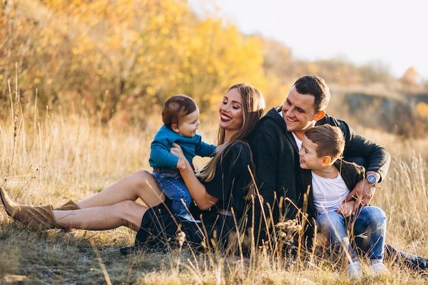 Junge familie mit zwei söhnen, die zusammen im park sitzen