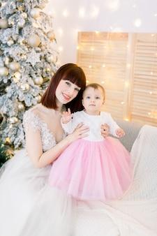 Junge familie, mutter mit baby, sitzend auf dem sofa, auf dem hintergrund des weihnachtsbaumes