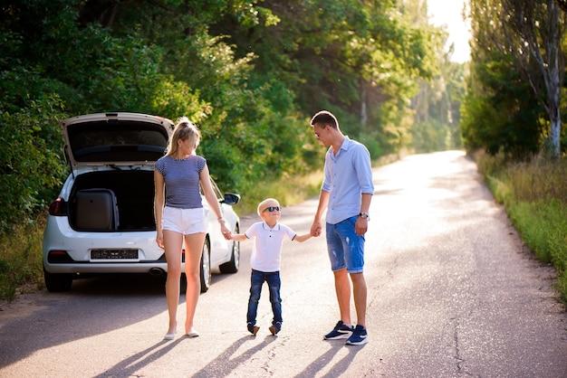 Junge familie reist mit dem auto. vater, mutter und kleiner sohn machen eine pause vom autofahren und gehen.