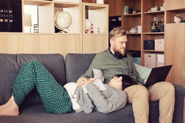 Junge familie, schwangere frau und mann mit laptop, der auf sofa am wohnzimmer sitzt. arbeiten in informeller umgebung, fernarbeit, home office, freiberufler, selbstisolation, aufschubidee