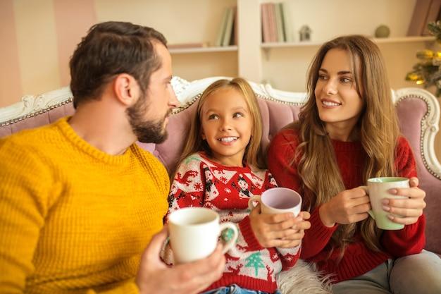 Junge familie sitzt auf dem sofa und fühlt sich wohl
