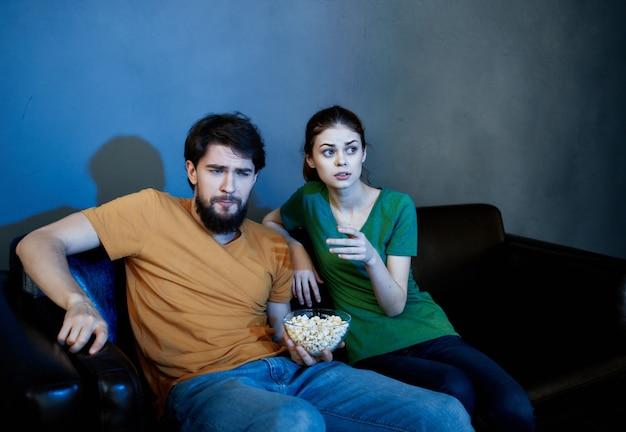 Junge familie sitzt auf der couch und schaut sich filme popcorn an
