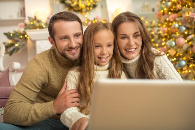 Junge familie sitzt, die aufgeregt schaut, während sie einen videoanruf hat