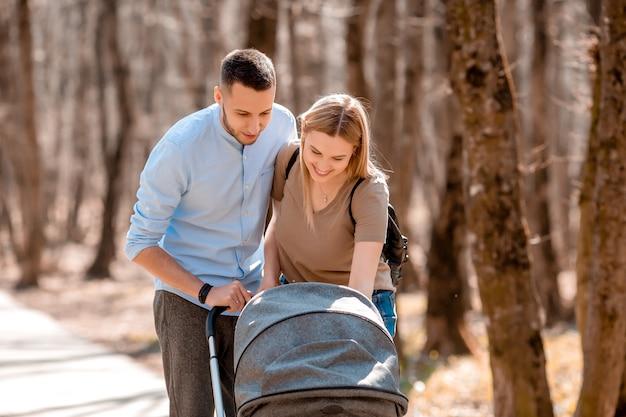 Junge familie spazieren im frühjahr im park mit einem kleinkind im kinderwagen. glückliche eltern