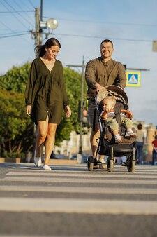 Junge familie überquert die straße auf einem zebrastreifen mit ihrem kleinen jungen, der in einem kinderwagen sitzt