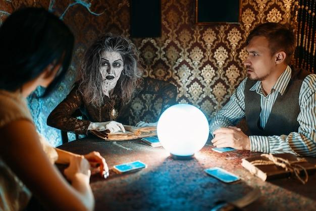 Junge familie und hexe am tisch mit kristallkugel auf spiritueller seance, gruseliger zauberer liest den zauber. weiblicher vorläufer ruft die geister