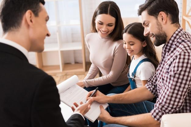 Junge familie unterzeichnet partnervereinbarung zum hauskauf