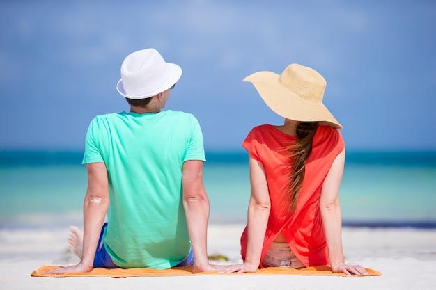 Junge familie von zwei auf weißem strand während der sommerferien