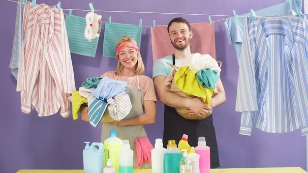 Junge familie wird wäsche waschen. der ehemann und die ehefrau sind bereit, haushaltsaufgaben zu übernehmen. studioaufnahme