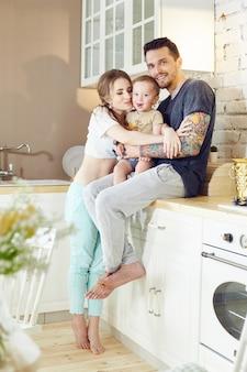 Junge familie zu hause morgens an einem freien tag. verheiratetes paar und ihr kleines baby baby in ihren armen. freudige und fröhliche gesichter, die sich umarmen und spaß haben