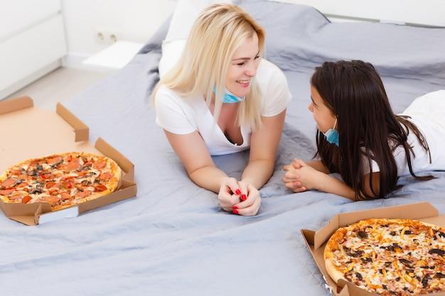 Junge familie zu hause, mutter und tochter kaufen während der quarantäne online lebensmittelpizza, konzeptlieferung