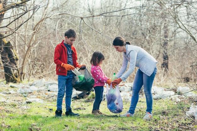 Junge familienmutter mit zwei kindern, die freiwillig den frühlingspark reinigen, müll und plastikflaschen sammeln