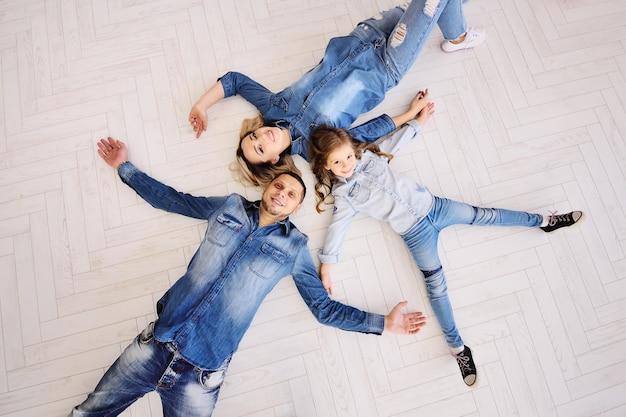 Junge familienmutter, -vater und -tochter liegen in jeanskleidung auf einem weißen boden in einer neuen wohnung