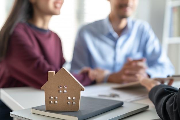 Junge familienpaare, die mit immobilienagentur über wohnungsbaudarlehensvertrags-kaufvertrag sprechen