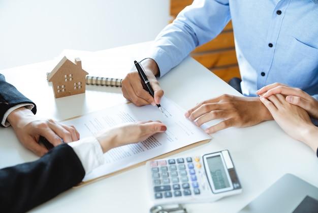 Junge familienpaare, die wohnungsbaudarlehensvertrags-kaufvereinbarung mit immobilienagentur unterzeichnen