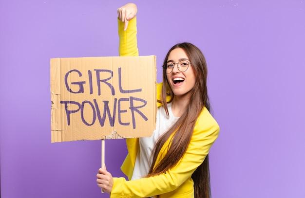 Junge feministische geschäftsfrau, die brett mit girl-power-text hält