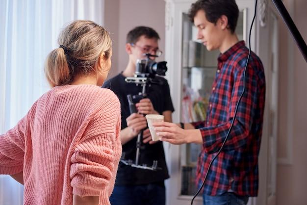 Junge filmemacher, die zu hause eine anzeige schießen