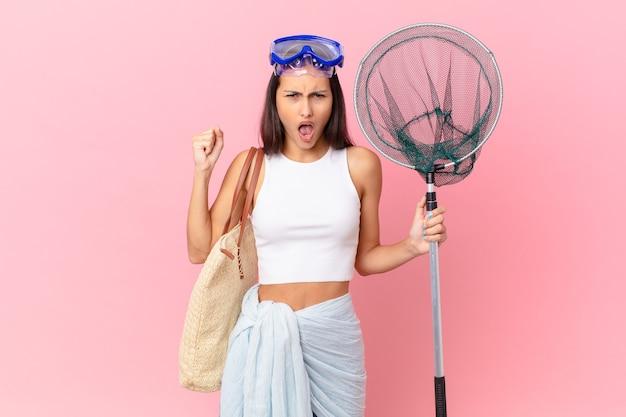 Junge fischerfrau, die aggressiv mit einem wütenden ausdruck und einer taucherbrille schreit