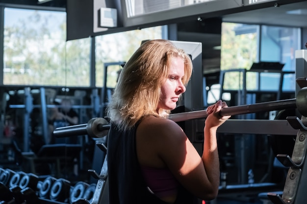 Junge fit frau an der turnhalle, die schwere übung macht. sportlerin in einem fitnessraum, der mit langhantel arbeitet
