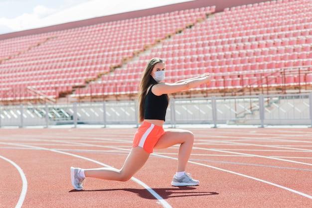 Junge fit frau in sportbekleidung und schutzmaske für coronavirus auf roter bahn und volleyballplatz