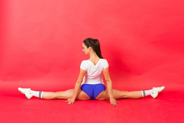 Junge fit turnerin in sportbekleidung trainieren