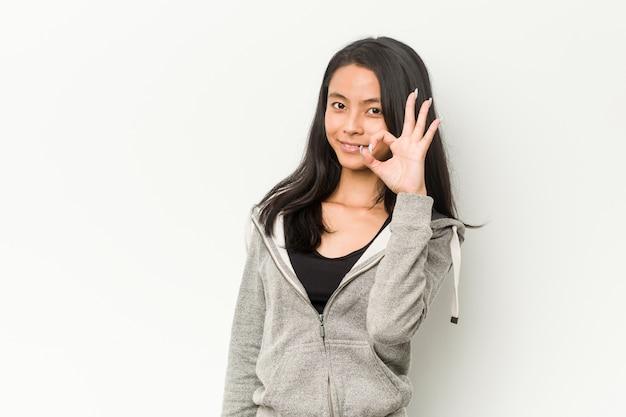 Junge fitness asiatische frau fröhlich und zuversichtlich zeigt ok geste