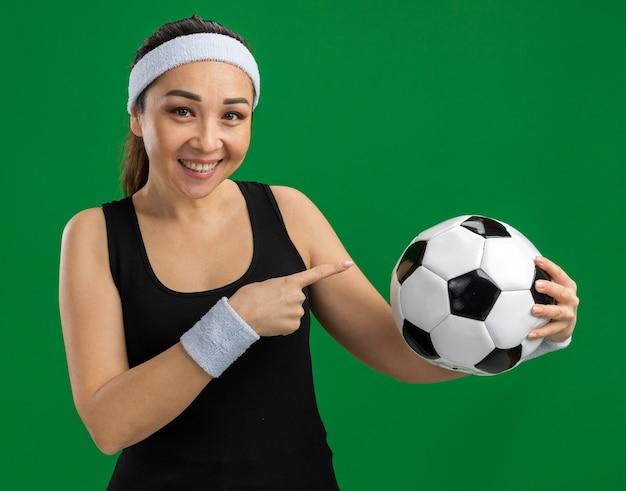 Junge fitness-frau mit stirnband, die fußball hält und mit dem zeigefinger darauf zeigt, lächelt fröhlich